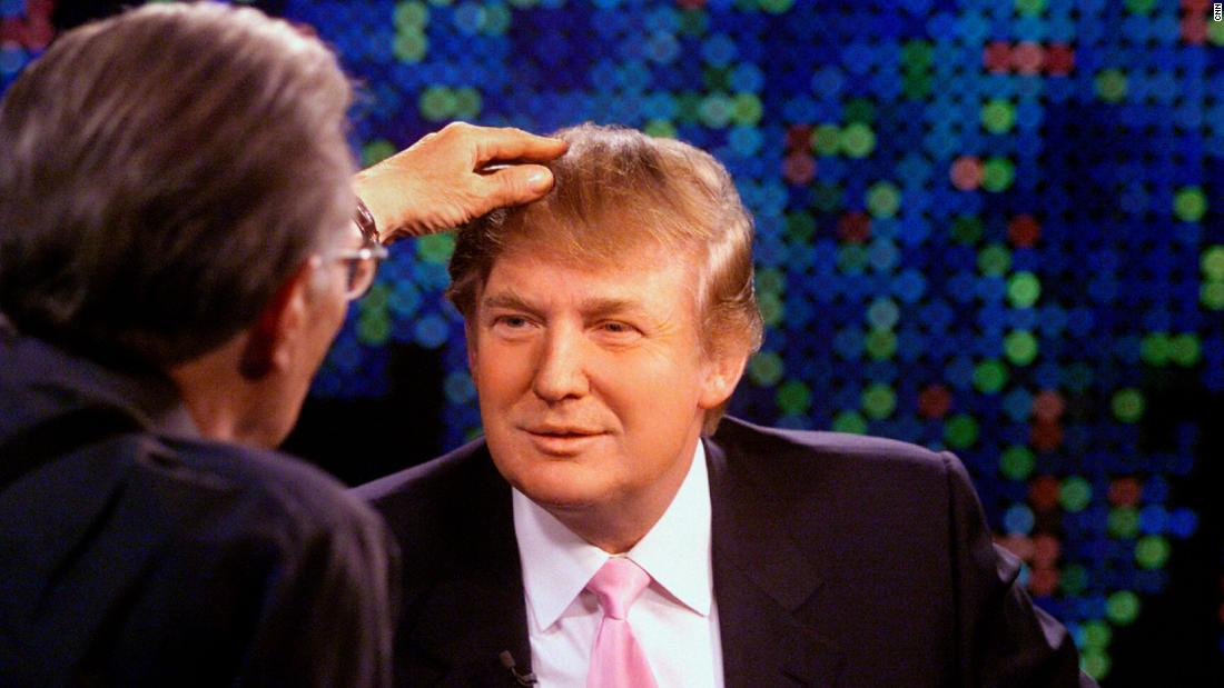 "King touches then-real estate developer Donald Trump's hair during an <a href=""https://www.cnn.com/videos/entertainment/2015/08/27/donald-trump-larry-king-live-president-hair-comb-over-bts.cnn"" target=""_blank"">interview in 2004</a>."