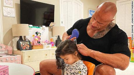 Dwayne Johnson and his daughter Tiana Gia as she lets him untangle her hair.