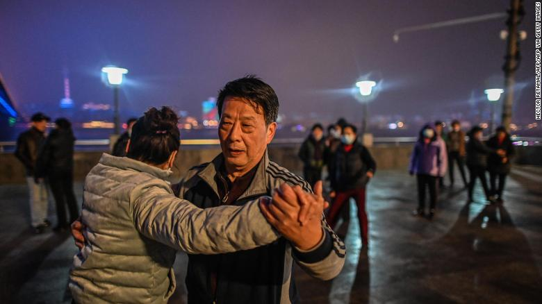 Elderly couples dance along the Yangtze River that cuts through the heart of the city.