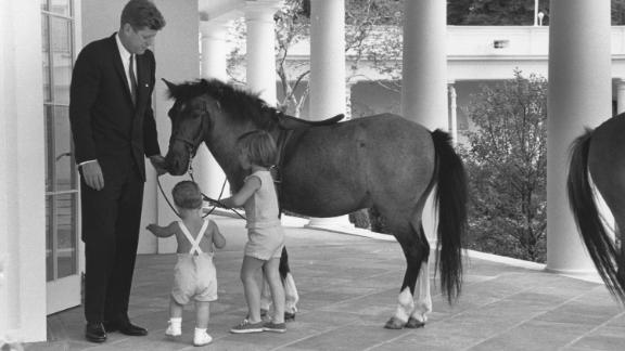 John F. Kennedy and his children John and Caroline play with their pony Macaroni in 1962.
