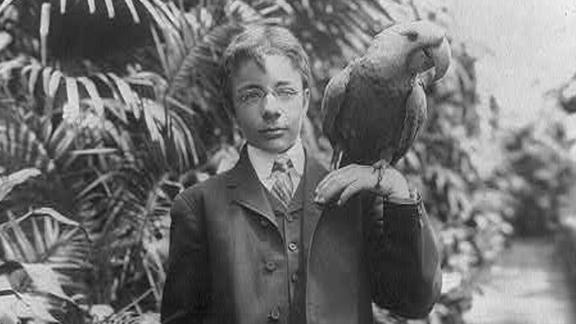 President Theodore Roosevelt's eldest son, Teddy Jr., holds a macaw named Eli circa 1902. The Roosevelts had all kind of animals, including lizards, snakes and a one-legged chicken.