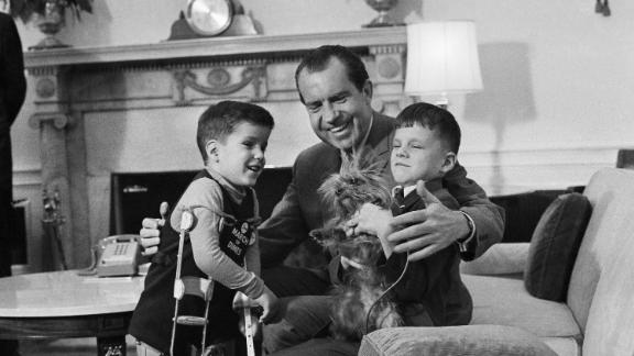 Richard Nixon shows off Pasha, his Yorkshire terrier, to two young visitors in 1969. Nixon also had two other dogs while in office.