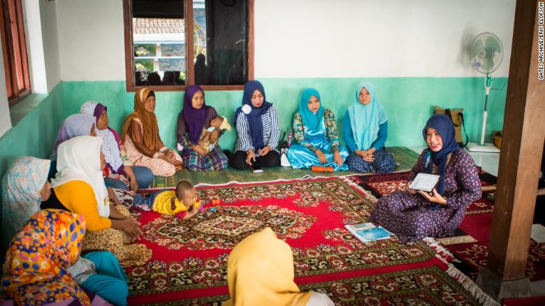 Ibu Suparti  demonstrates the tablet to other women at a community center in Dompyongan, Klaten, Indonesia, in 2017.
