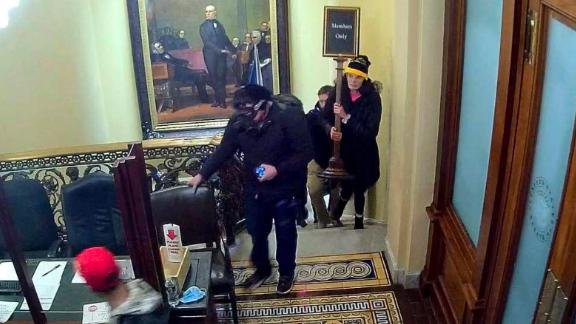 """In an image taken from surveillance video, Courtright is seen w on the walking up the steps near the Senate Chamber \ carrying a """"Members Only"""" sign."""