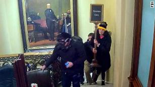 "In an image taken from surveillance video, Gracyn Courtright is seen walking up the steps near the Senate Chamber carrying a ""Members Only"" sign."