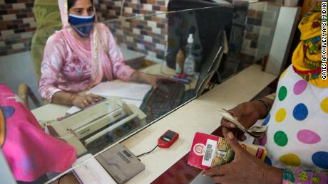 A business correspondent agent helps a woman with a bank transaction in Silana, India.