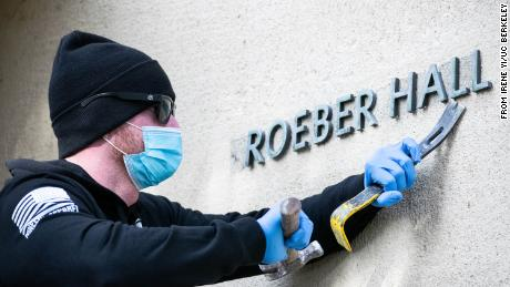A campus worker removes letters from the exterior of Kroeber Hall on Tuesday, January 26.