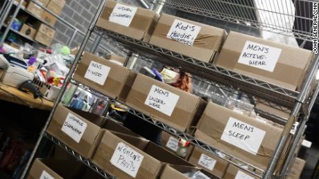 An employee sorts through a pile of returns and categorizes each item to eventually be sold to a reseller.