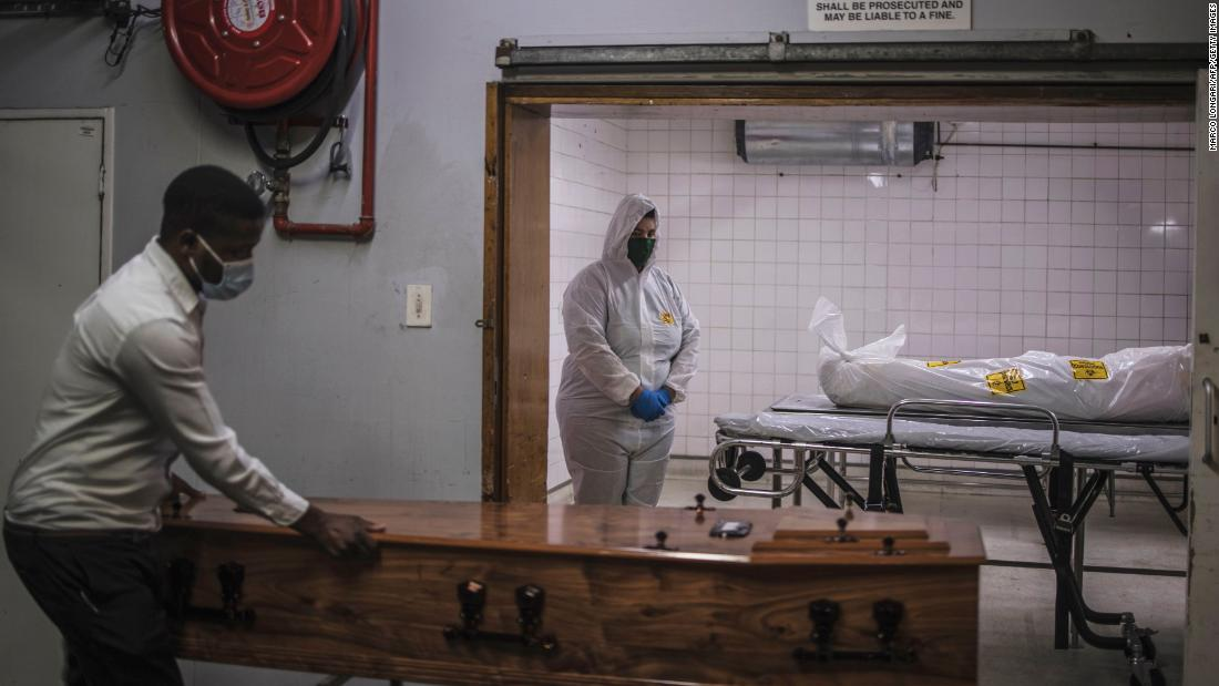 A morgue attendant, right, stands next to the body of a Covid-19 victim in Pretoria, South Africa, on January 22.