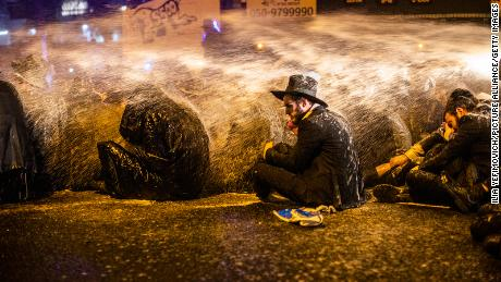 Israeli policemen use water cannon to disperse an anti-lockdown demonstration staged in Bnei Brak by ultra-Orthodox Jews on December 27.