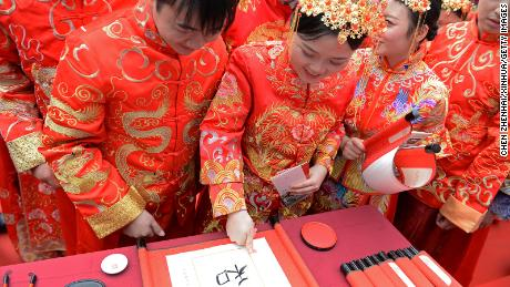 A couple marks fingerprints on ceremonial calligraphy during a traditional group wedding in Changsha, China.