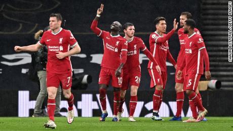 Mane celebrates with Andrew Robertson and teammates after he scores his sides third goal against Tottenham.