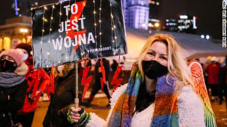 """Corporate worker Eliza carries a placard saying """"This is war"""" at Friday's protest."""
