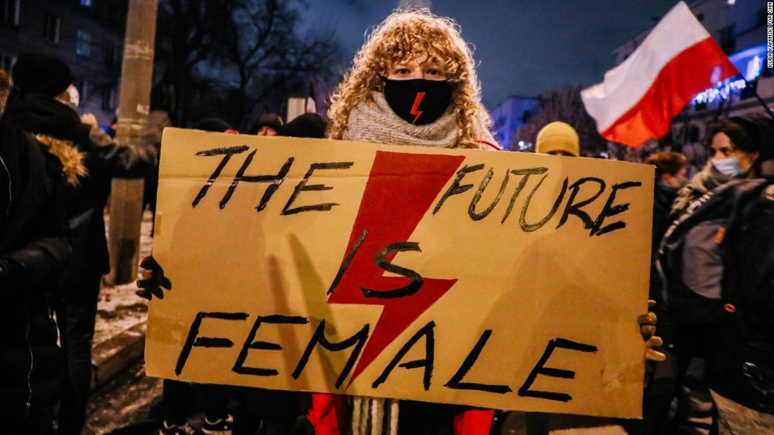 Weronika, 22, holds a banner with the Women's Strike symbol.
