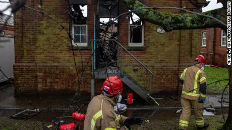 Firefighters inspect the charred remains of a block at Napier Barracks in Folkestone, England, on January 30, 2021