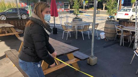 Angela Marsden of the Pineapple Hill Saloon and Grill in Sherman Oaks, California, measures the distance between tables at her outdoor dining area.