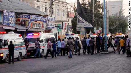Ambulances and security forces gather on the street outside the Afrik hotel in Mogadishu after an explosion and an attack by gunmen