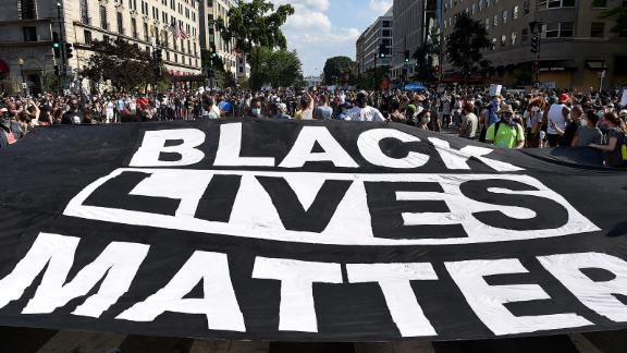 """Demonstrators deploy a """" Black Lives Matter"""" banner near the White House  during a demonstration against racism and police brutality, in Washington, DC on June 6, 2020. - Demonstrations are being held across the US following the death of George Floyd on May 25, 2020, while being arrested in Minneapolis, Minnesota. (Photo by Olivier DOULIERY / AFP) (Photo by OLIVIER DOULIERY/AFP via Getty Images)"""