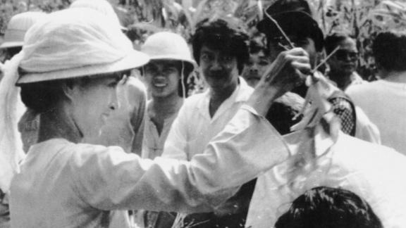 Suu Kyi sprinkles water over the heads of her followers during a traditional new year ceremony in Yangon in 1989. Five days of celebrations were marked by anti-government protests closely watched by armed troops.
