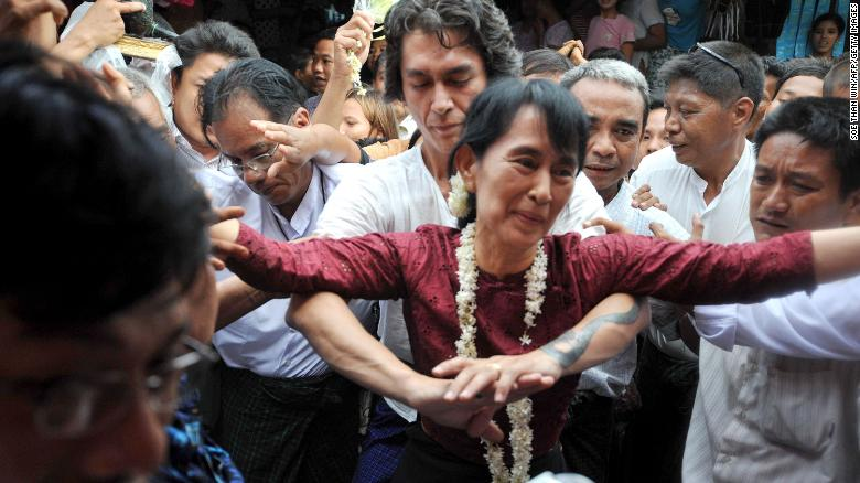 Suu Kyi is held by her son Kim Aris as she is greeted by supporters during a visit to the ancient temple city of Bagan in 2011.