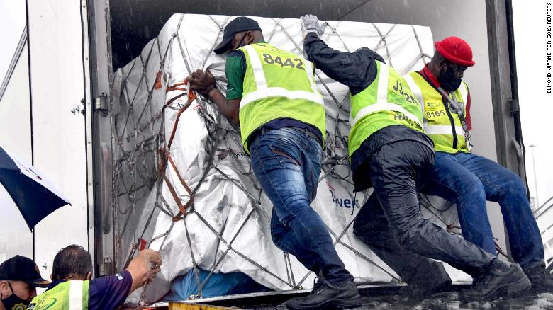 Workers load South Africa's first coronavirus  vaccine doses as they arrive at an airport in Johannesburg, South Africa, in this handout picture taken February 1, 2021.