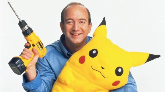 Bezos holds a power drill and a stuffed Pikachu in 1999. By this point, Amazon had started to sell items other than books.