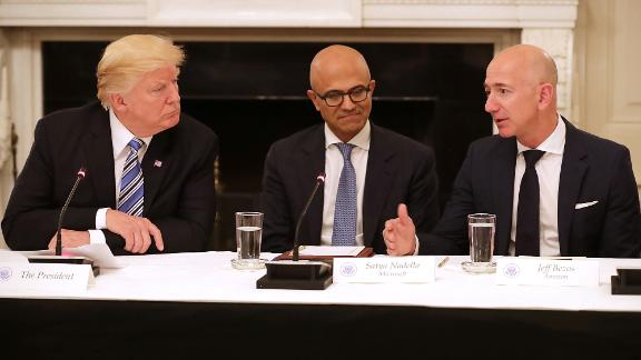 """US President Donald Trump and Microsoft CEO Satya Nadella listen to Bezos at a White House meeting of the American Technology Council in 2017. According to the White House, the council's goal is """"to explore how to transform and modernize government information technology."""""""