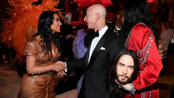 Bezos shakes hands with Kim Kardashian West while attending the Met Gala in New York in 2019. Actor Jared Leto is on the right.