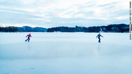 Two men skate on an icy lake in Trondheim, Norway.
