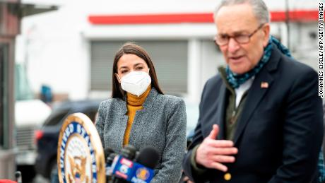 Schumer speaks as Democratic Congresswoman from New York Alexandria Ocasio-Cortez wearing a face mask to protect herself from the coronavirus, listens during a press conference in the Corona neighbourhood of Queens on April 14, 2020 in New York City.