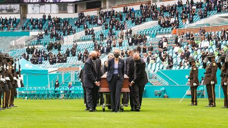 Schwartzenberger's casket is wheeled on the the field past saluting law enforcement officers.