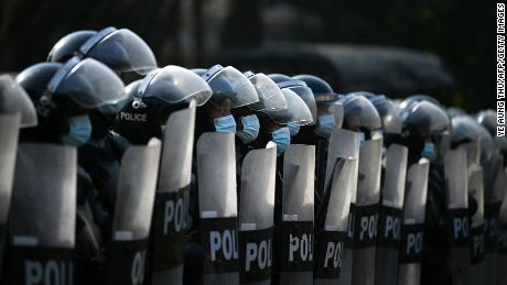 Riot police block the street as protesters hold a demonstration against the military coup in Yangon on February 7, 2021.