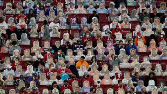 Fans sit among cardboard cutouts before the game.