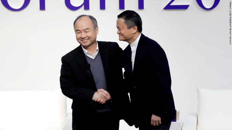 Masayoshi Son dan Jack Ma berjabat tangan di sebuah forum di Tokyo pada tahun 2019.