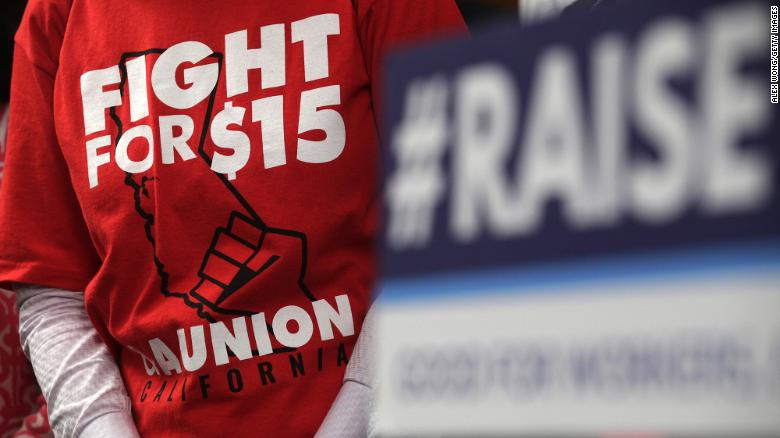 """An activist wears a """"Fight For $15"""" T-shirt during a news conference prior to a vote on the Raise the Wage Act July 18, 2019 at the U.S. Capitol in Washington, DC. The legislation would raise the federal minimum wage from $7.25 to $15 by 2025.  (Photo by Alex Wong/Getty Images)"""