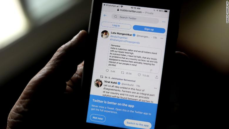 A man reads tweets by Indian celebrities, one of the many backing the Indian government, on his mobile in New Delhi, India, on Thursday.