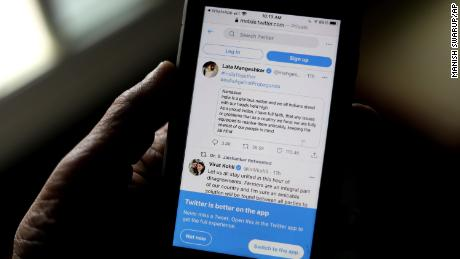 A man on Thursday in New Delhi, India, reads the tweets of Indian celebrities who are one of the Indian government's supporters on his mobile phone.