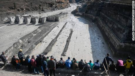 People look at the remains of a dam along a river in Tapovan of Chamoli district on Tuesday, destroyed after an avalanche.