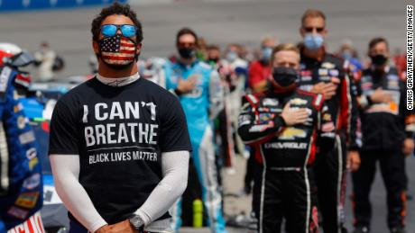 "Bubba Wallace wears a ""I Can't Breathe - Black Lives Matter"" T-shirt under his fire suit in solidarity with protesters around the world taking to the streets after the death of George Floyd on May 25 while in the custody of Minneapolis, Minnesota police, stands during the national anthem prior to the NASCAR Cup Series Folds of Honor QuikTrip 500 at Atlanta Motor Speedway on June 07, 2020 in Hampton, Georgia."
