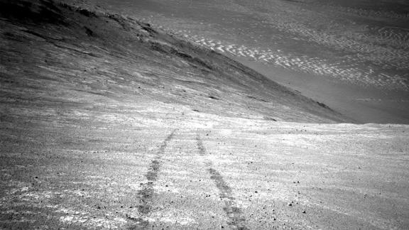 From its perch high on a ridge, Opportunity recorded this 2016 image of a Martian dust devil twisting through the valley below. The view looks back at the rover's tracks leading up the north-facing slope of Knudsen Ridge, which forms part of the southern edge of Marathon Valley.