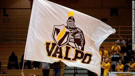 A Valparaiso University cheerleader waves a Valparaiso Crusaders flag.