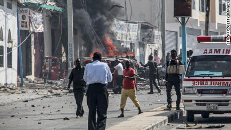 Security officers stand around the site of the car bomb attack in Mogadishu on February 13, 2021.