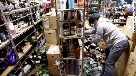 A liquor shop's manager clears damaged bottles following Saturday's quake.