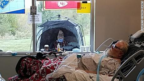 Roger Collins lies in his hospital bed while his wife, Billie, sits in a tent on the other side of the window.