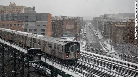 A subway train travels on the elevated track over snow-covered streets in the Bronx borough of New York City on Sunday, February 7.