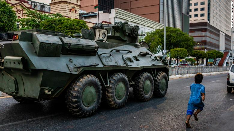 A child runs alongside a military armored vehicle moving along a street on February 14, 2021 in Yangon, Myanmar.