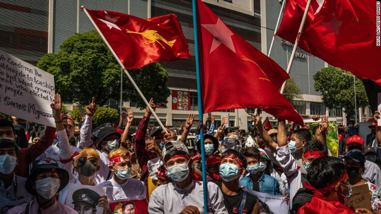 Protesters hold placards and shout slogans near the City Hall on February 13, 2021 in Yangon, Myanmar.