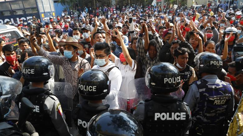 Residents and protesters face riot police as they question them about recent arrests made in Mandalay, Myanmar,  February 13, 2021.