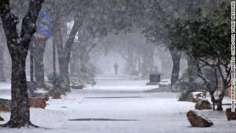 A pedestrian walks through the snow on the Angelo State University campus in Texas Sunday.