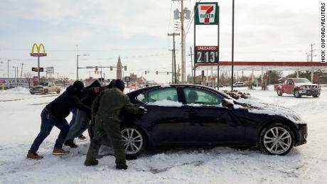 People work to free a stuck motorist in Oklahoma City on February 15, 2021.